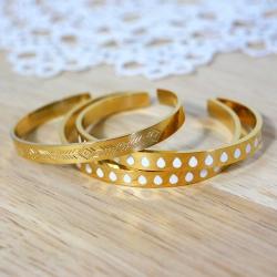 Bracelets rigides en métal doré gravé et émaillé de gouttes blanches