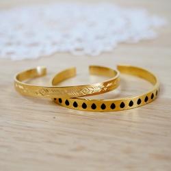 Bracelets rigides en métal doré gravé et émaillé de gouttes noires